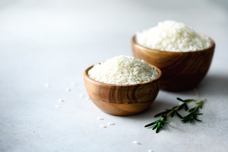 White raw organic jasmine rice in wooden bowl and rosemary on light concrete background. Food ingredients. Copy space. Stock Photo
