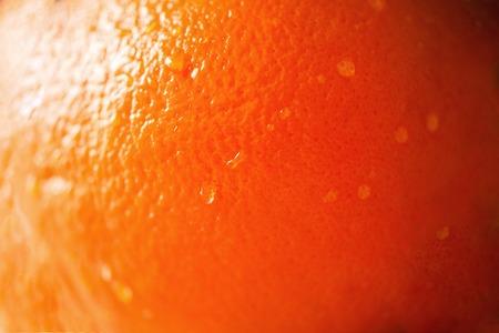 Texture of fresh bright orange peel, closeup, copy space. Macro of orange fruit. Citrus fruit background