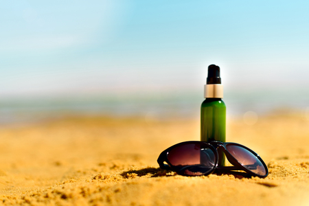 Sunglasse, sunscreen cream on yellow sand beach against sea background with copyspace. Vacation and travel wallpaper. Skin care concept. Stock Photo