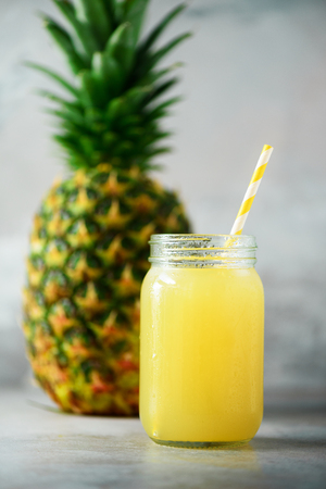 Glass jar of pineapple smoothie and whole fruit on gray background. Copy space. Summer, holiday concept. Raw, vegan, vegetarian, clean eating diet.