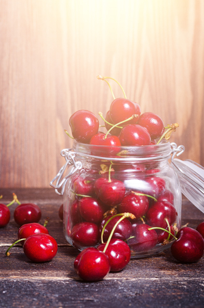Red cherries in a glass jar on dark wooden background with copy space. Sunny summer and harvest concept. Cherry macro. Sunlight affect. Vegan, vegetarian, raw food Stock Photo