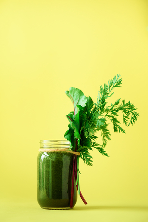 Smoothie with beet greens and carrot tops on yellow background, copy space. Summer vegan food concept. Healthy detox eating, alkaline diet. Fresh squeezed juice, drink from vegetables. Leafy greens.