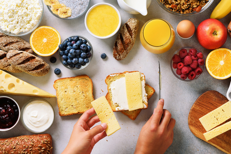 Female hands spreading butter on bread. Woman cooking breakfast. Healthy breakfast ingredients, food frame. Granola, egg, nuts, fruits, berries, milk, yogurt, juice, cheese. Top view, copy space