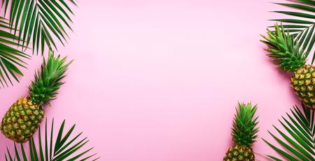 Ananas en tropische palmbladeren op pittige pastelroze achtergrond. Zomer concept. Creatieve plat leggen met kopie ruimte. Bovenaanzicht.