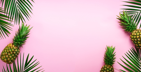 Pineapples and tropical palm leaves on punchy pastel pink background. Summer concept. Creative flat lay with copy space. Top view. Stock Photo - 104932013