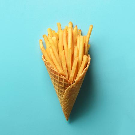 파란색 배경에 와플 콘에 튀긴 감자입니다. 토마토 소스를 곁들인 매운 짭짤한 감자 튀김. 패스트 푸드, 정크 푸드, 다이어트 개념. 평면도. 최소한의 스타일. 팝 아트 디자인, 창의적인 개념