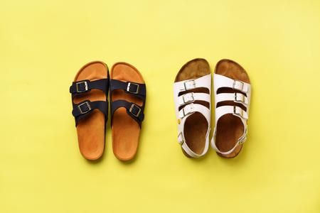 Scarpe estive femminili - sandali (birkenstock) e pantofole su sfondo giallo con spazio di copia. Vista dall'alto. Disposizione piatta minima. Concetto di selezione