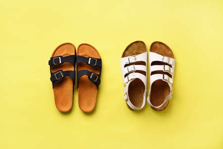 Summer female shoes - sandals (birkenstock) and slippers on yellow background with copy space. Top view. Minimal flat lay. Selection concept Banco de Imagens - 104963932