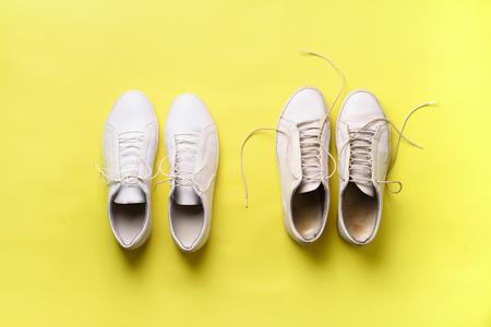 Alte schmutzige Turnschuhe gegen neue weiße Turnschuhe auf gelbem Hintergrund. Trendiges Schuhwerk. Draufsicht. Konzept von Erfahrung, Disziplin und Chaos, Genauigkeit \ Chaos, stilvolle Schuhe. Zurück zur Schule.