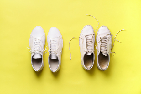 Old dirty sneakers vs new white sneakers on yellow background. Trendy footwear. Top view. Concept of experience, discipline and chaos, accuracy \ mess, stylish shoes. Back to school.