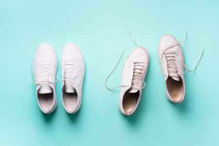 Old dirty sneakers vs new white sneakers on blue background. Trendy footwear. Top view. Concept of experience, discipline and chaos, accuracy \ mess, stylish shoes. Back to school.