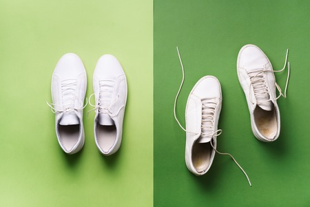 Old dirty sneakers vs new white sneakers on green background. Trendy footwear. Top view. Concept of experience, discipline and chaos, accuracy \ mess, stylish shoes. Back to school.