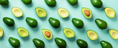 Avocado pattern on blue background. Top view. Banner. Pop art design, creative summer food concept. Green avocadoes, minimal flat lay style. Banner. 写真素材