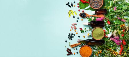 Approccio di medicina olistica. Cibo sano, integratori alimentari, erbe curative e fiori. Curcuma, lavanda essiccata, polvere di spirulina in ciotole di legno, bacche fresche, capsule di acido omega.