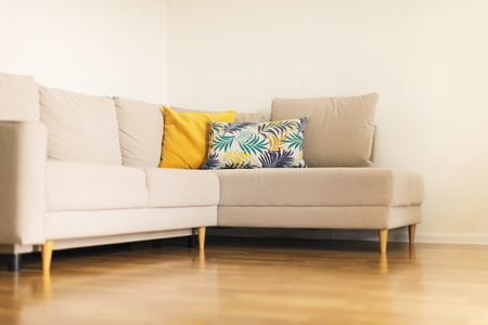 Modern beige sofa, yellow and blue pillows with tropical palms, monstera pattern in living room with white walls. Copy space Design interior