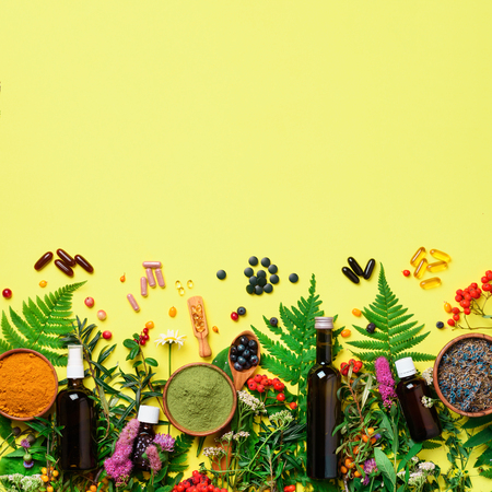 Alternative medicine. Holistic approach. Healing herbs and flowers over yellow background. Top view, copy space, flat lay. Banner. Square crop.