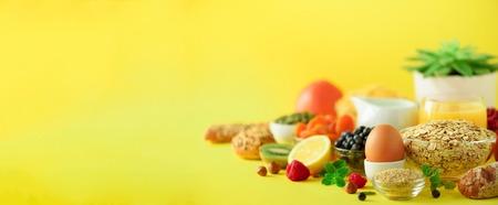 Delicious breakfast ingredients. Soft boiled egg, oat flakes, nuts, fruits, berries, milk, yogurt, orange, banana, peach on yellow background.