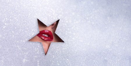 View of bright lips with glitter through hole in silver paper background.