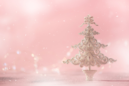Silver glitter Christmas tree on pink background with lights bokeh, copy space. Greeting card for new year party. Festive holiday concept.