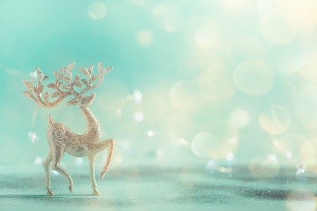 Silver glitter Christmas deer on blue background with lights bokeh, copy space. Greeting card for new year party. Festive holiday concept. Banner.