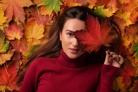 Girl holding red maple leaf in hand over colorful fallen leaves background. Top view. Copy space for advertising. Sunny day, warm weather. Gold cozy autumn concept.
