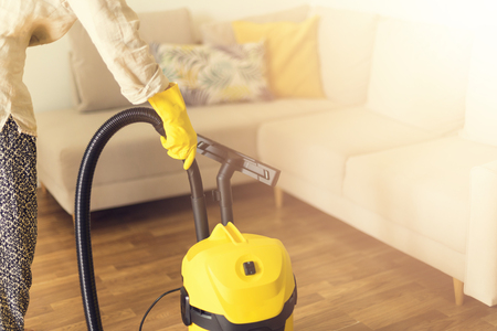 Woman in protective gloves cleaning the living room with yellow vacuum cleaner. Copy space. Clean concept. Stock Photo