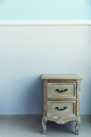 Room interior with bedside table on pastel blue wall. Minimalistic background, copy space