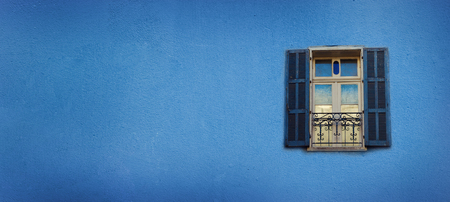 Old blue painted windows on concrete wall. Banner with copy space. Pop art concept, greek style window.