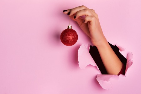 Woman holding red glittering Christmas ball in hand over pink background with snow, light bokeh. Banner, copy space. New year holiday celebration concept