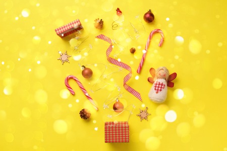 Greeting card with snow, lights bokeh for New year party. Christmas gifts, decorative elements and ornaments on yellow background. Top view. Winter holiday concept.