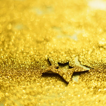 Christmas celebration. Abstract background for new year party. Patter of gold stars with lights, bokeh. Square crop. Golden glitter stars on yellow shimmer texture. 版權商用圖片