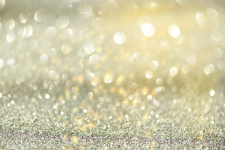 Gold and silver abstract bokeh lights. Shiny glitter background with copy space. New year and Christmas concept. Sparkling greeting card. Stock Photo