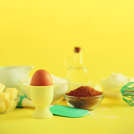Bakery food frame, cooking concept. Different baking ingredients - butter, sugar, flour, milk, eggs, oil, spoon, rolling pin, brush whisk over yellow background Square crop Copy space