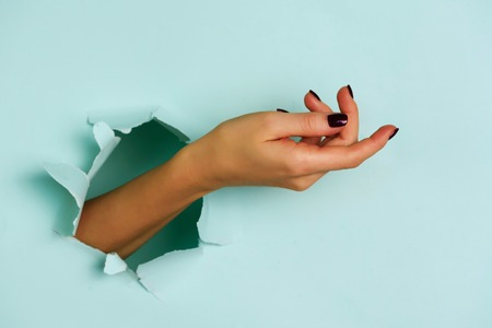 Mano di donna che salta fuori dalla carta blu del buco Archivio Fotografico