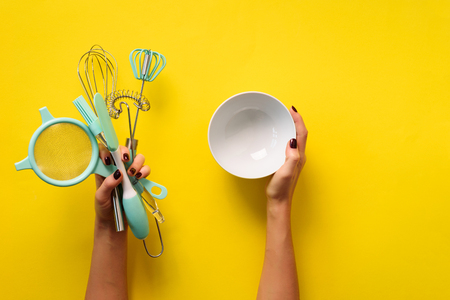 Female hand holding sieve flour on yellow