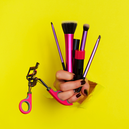 Woman hand with professional cosmetic tools for make up: brushes, mascara, lipstick, eyelash curler on yellow background. Beauty concept for cosmetics sale. Square crop.