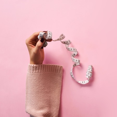 Female hands holding measuring tape over pink