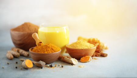Yellow turmeric latte drink. Golden milk with cinnamon, turmeric, ginger over grey 스톡 콘텐츠 - 116989639