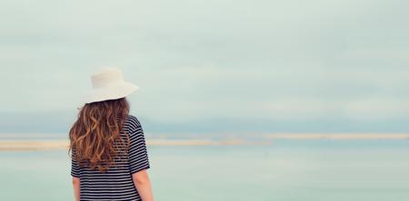 Woman in sailor striped dress near seaside of Dead Sea beach. 版權商用圖片