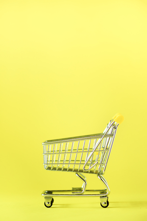 Shopping cart on yellow background. Minimalism style. Creative design. Copy space. Shop trolley at supermarket. Sale, discount, shopaholism concept. Consumer society trend.