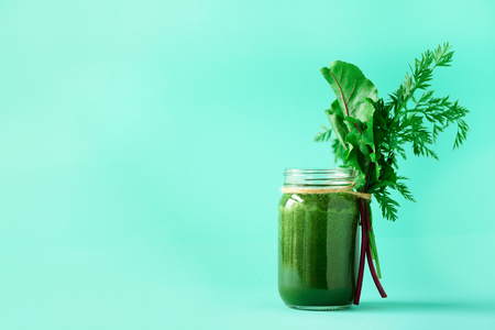 Smoothie with beet greens and carrot tops on blue background, copy space. Summer vegan food concept. Healthy detox eating, alkaline diet. Fresh squeezed juice, drink from vegetables. Leafy greens. Reklamní fotografie