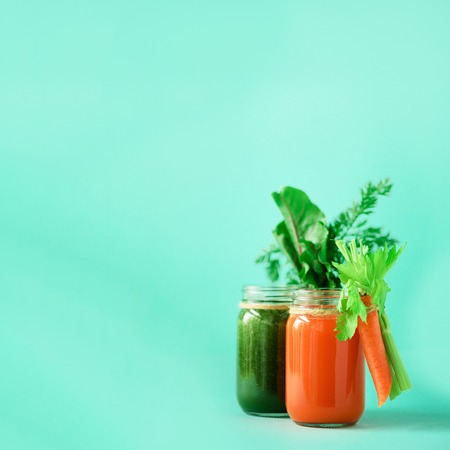 Healthy organic green and orange smoothies on blue background. Square crop. Detox drinks in glass jar from vegetables - carrot, celery, beet greens and tops. Copy space. Summer food concept Imagens