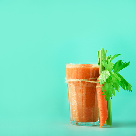 Fresh organic carrot juice with carrots, celery on blue background. Square crop. Vegetable smothie in glass. Banner. Copy space. Summer food concept. Healthy detox eating, alkaline diet