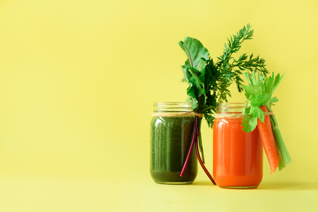 Healthy organic green and orange smoothies on yellow background. Detox drinks in glass jar from vegetables - carrot, celery, beet greens and tops. Copy space. Summer food concept.