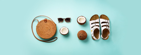 Stylish rattan bag, coconut,  palm branches, sunglasses on blue background. Banner. Top view with copy space. Trendy bamboo bag and white shoes. Summer fashion flat lay.