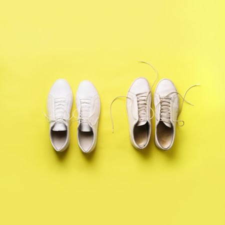 Old dirty sneakers vs new white sneakers on yellow background. Trendy footwear. Square crop. Top view. Concept of experience, discipline and chaos, accuracy \ mess, stylish shoes. Back to school.