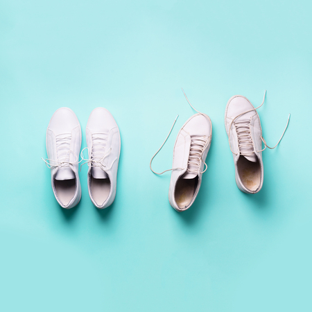 Old dirty sneakers vs new white sneakers on blue background. Trendy footwear. Square crop. Top view. Concept of experience, discipline and chaos, accuracy \ mess, stylish shoes. Back to school.