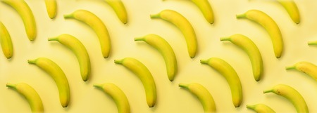 Geometric colorful fruit pattern. Bananas over yellow background. Top view. Pop art design, creative summer concept. Minimal flat lay style. Banner.