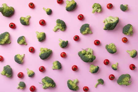 Creative layout of fresh broccoli, tomatoes on pink paper background. Top view. Food pattern in minimal style. Flat lay. Banner. Zdjęcie Seryjne