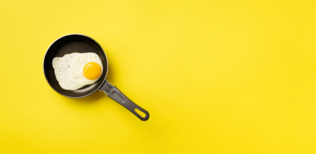 Creative food concept with fried egg on pan over yellow background. Top view. Creative pattern in minimal style. Flat lay